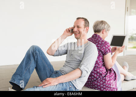 Mature man talking on cell phone and mature woman using digital tablet, smiling - Stock Photo