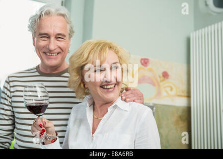 Mature couple drinking wine, smiling - Stock Photo