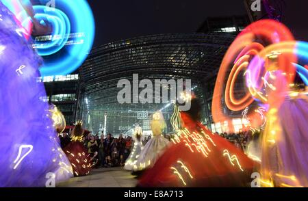 Berlin, Germany. 2nd Oct, 2014. Women dance in illuminated dresses in from of the main train station in Berlin, - Stock Photo