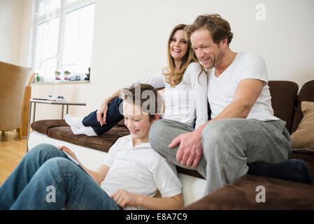 Happy family in living room with digital tablet - Stock Photo