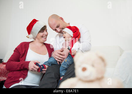 Toddler with Christmas cap in the arms of his father - Stock Photo