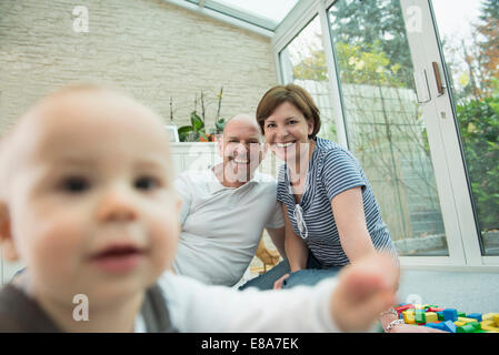Parents and little son sitting on ground of living room - Stock Photo