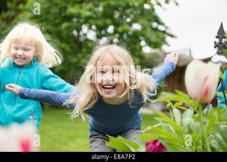 Two blonde kids sisters playing in garden - Stock Photo