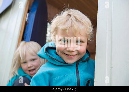 Portrait of two smiling young blonde kids - Stock Photo