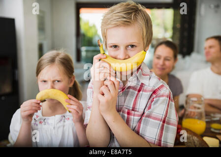 Brother and sister having fun with two bananas - Stock Photo