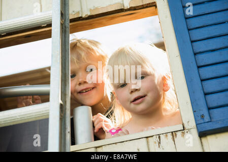 Little boy and girl looking out of tree house - Stock Photo