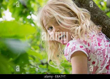 Young girl sitting in tree sticking tongue out - Stock Photo