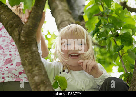Small blonde girl sitting in cherry tree laughing - Stock Photo