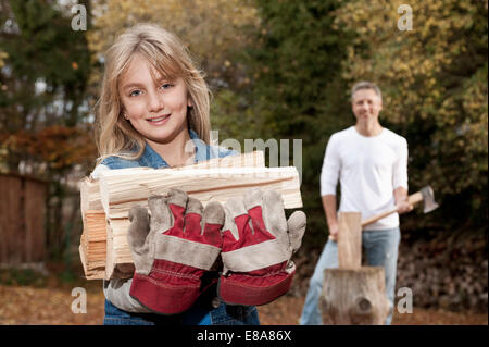 Smiling girl carrying firewood with father in background - Stock Photo