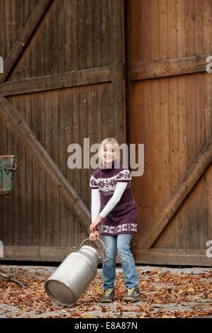 Smiling girl pulling milk churn on farm - Stock Photo