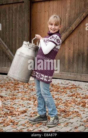Smiling girl carrying milk churn on farm - Stock Photo