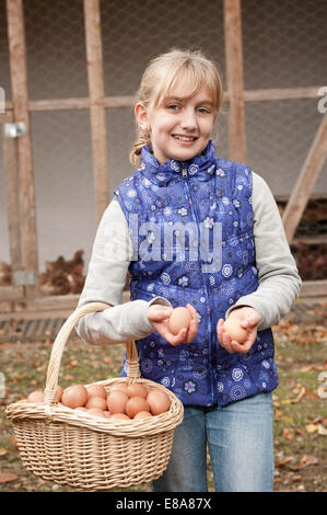 Blond girl holding basket with eggs on farm - Stock Photo