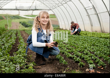 Smiling blond girl in greenhouse - Stock Photo