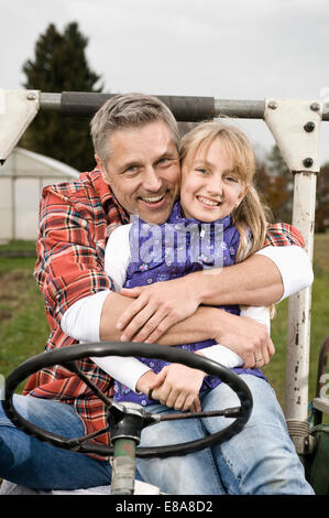 Farmer hugging daughter on tractor - Stock Photo