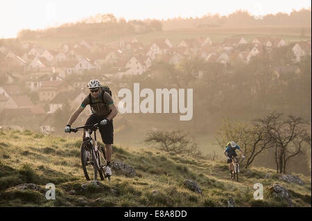 Young men mountainbiking at sunrise, Bavaria, Germany - Stock Photo
