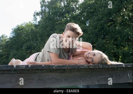 Teenage couple lying on a jetty at lake - Stock Photo