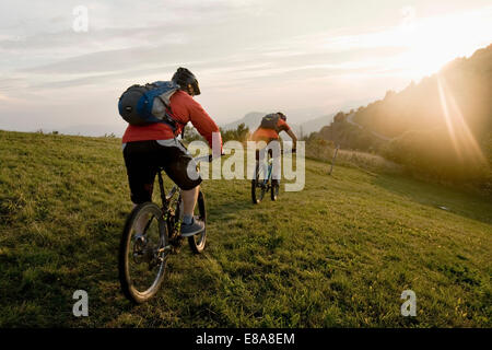 two mountain bikers on the way at sunset, Kolovrat, Istria, Slovenia - Stock Photo