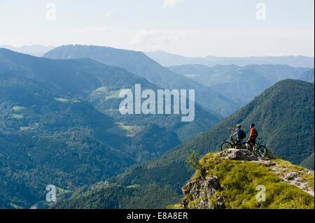 two mountain bikers looking at view, Slatnik, Istria, Slovenia - Stock Photo
