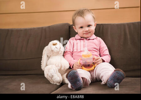 Baby girl 18 months old sitting on sofa toy rabbit - Stock Photo