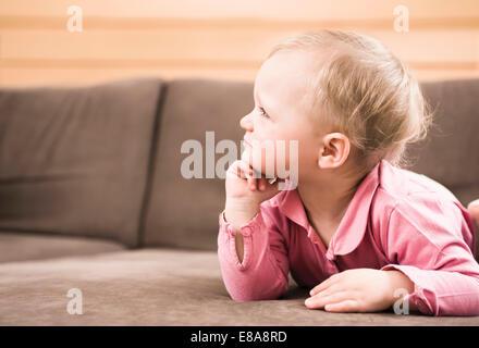 Baby girl lying sofa on thinking side profile - Stock Photo