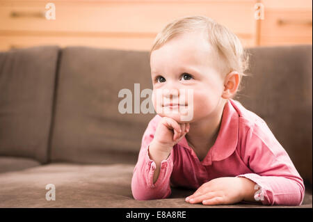 Baby girl 18 months old sofa thinking portrait - Stock Photo