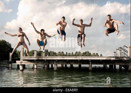 Five teenagers jumping from a jetty into lake - Stock Photo
