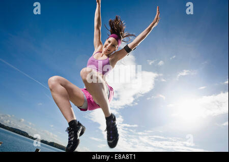 Woman jumping on jetty, Woerthsee, Bavaria, Germany - Stock Photo