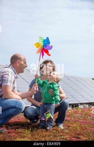 Baby holding toy windmill symbolic energy - Stock Photo