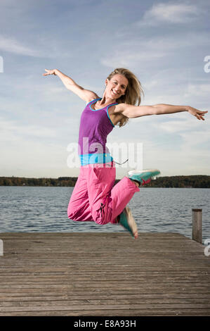 Woman dancing Zumba on jetty, Woerthsee, Bavaria, Germany - Stock Photo