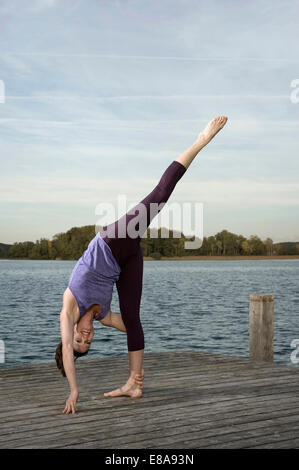 Woman practicing yoga on jetty, Woerthsee, Bavaria, Germany - Stock Photo