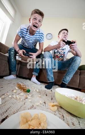 Two teenage boys playing video game - Stock Photo