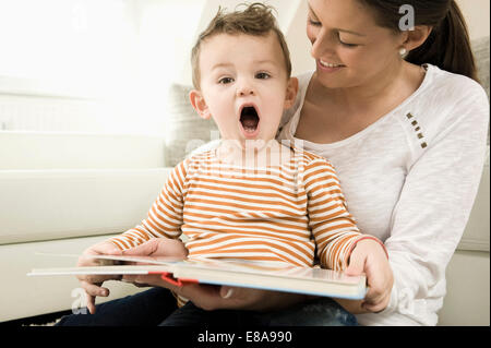 Mother and son are watching storybook, smiling - Stock Photo
