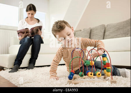Boy playing game while mother sitting on sofa - Stock Photo