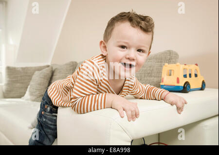 Portrait of boy playing with toys, smiling - Stock Photo