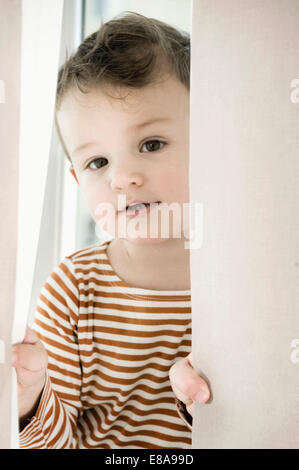 Portrait of boy playing with curtain - Stock Photo