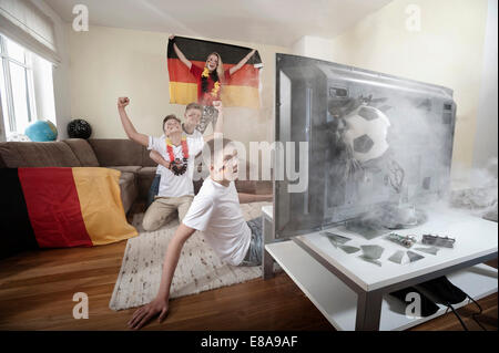 Teenage soccer fans in living room with ball demolishing TV - Stock Photo