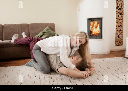 Teenage couple playfighting on carpet in front of fireside - Stock Photo
