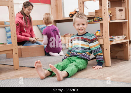 Little boy sitting on the ground in his kindergarten - Stock Photo