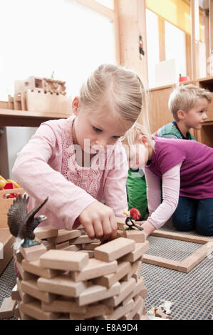 Little girl playing with wooden building bricks in her kindergarten - Stock Photo