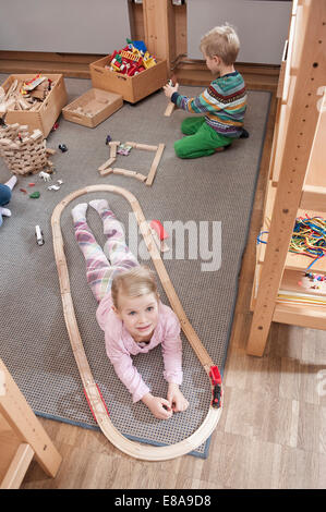 Little girl playing with wooden railroad in her kindergarten - Stock Photo