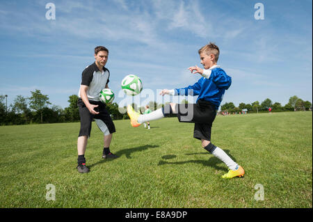 Soccer trainer teaching young player helping - Stock Photo