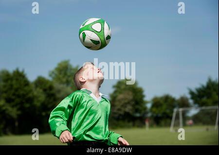 Young boy soccer practice football header ball - Stock Photo