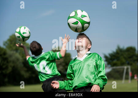 Two young football players learning ball control - Stock Photo