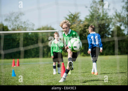 Boys junior soccer team practicing penalty - Stock Photo