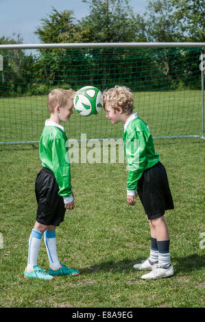 Two young soccer players learning ball control - Stock Photo