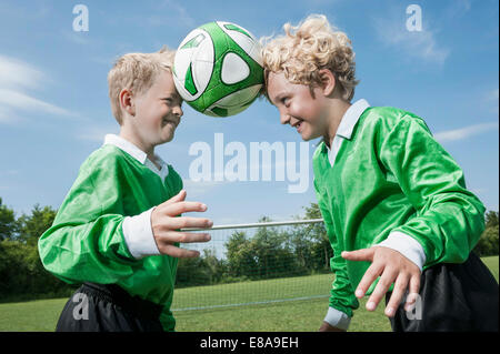 Two junior soccer players learning ball control - Stock Photo