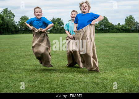 Three young boys running in sackrace jumping - Stock Photo