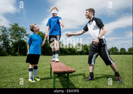Soccer coach teaching young player trust - Stock Photo