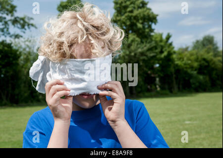Young blonde boy holding removing blindfold - Stock Photo