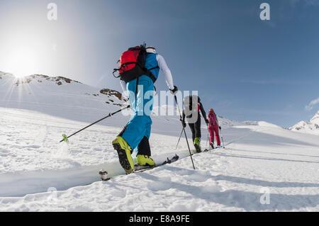 Three skiers climbing steep slope snow winter - Stock Photo